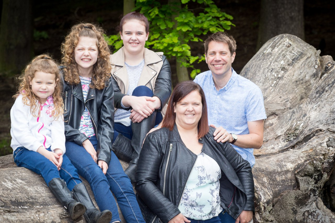 group family photo next to fallen tree in woodland