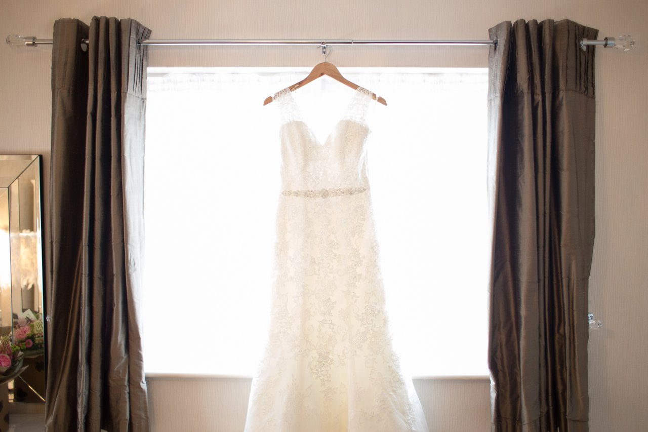 Ivory wedding dress hanging against window