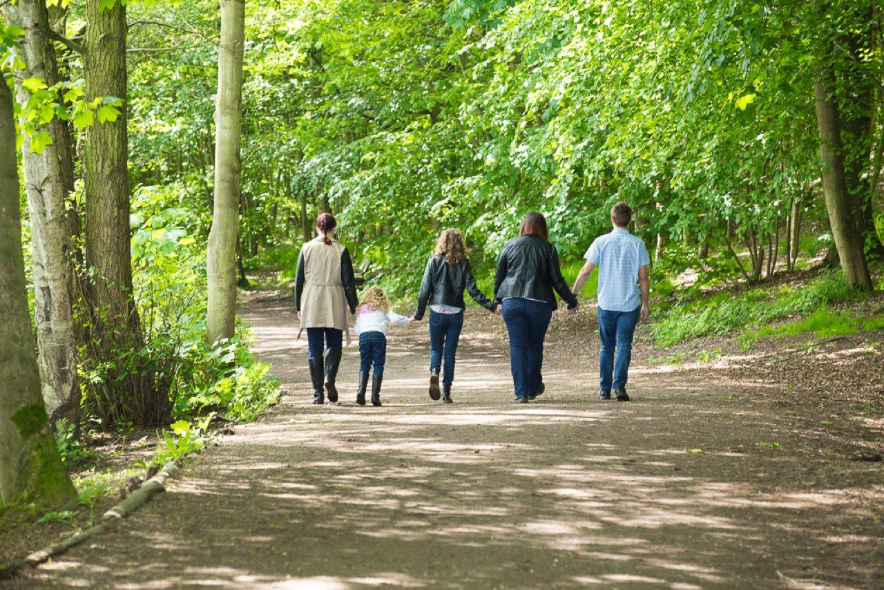 family walking away in sunlight towards trees