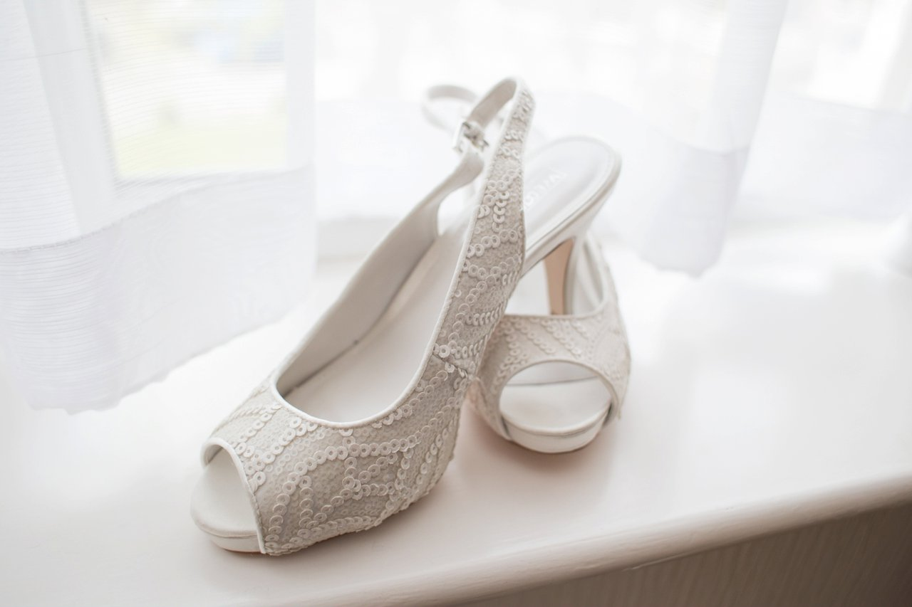 white wedding shoes on window sill