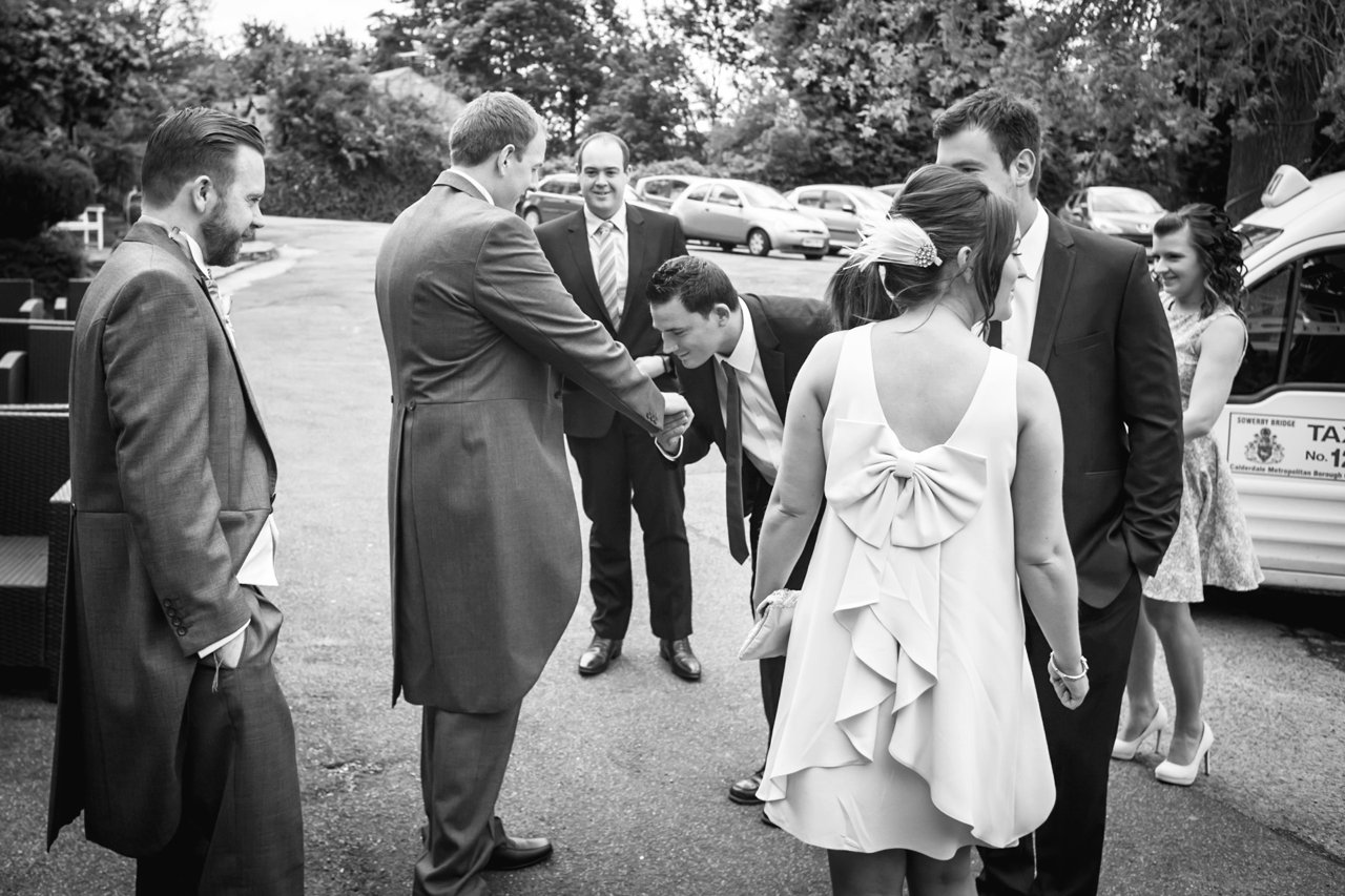 Wedding guest jokingly kissing grooms hand