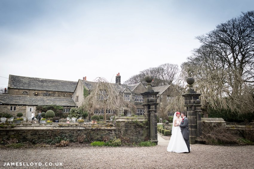 bride and groom in front of Holdsworth House blue sky