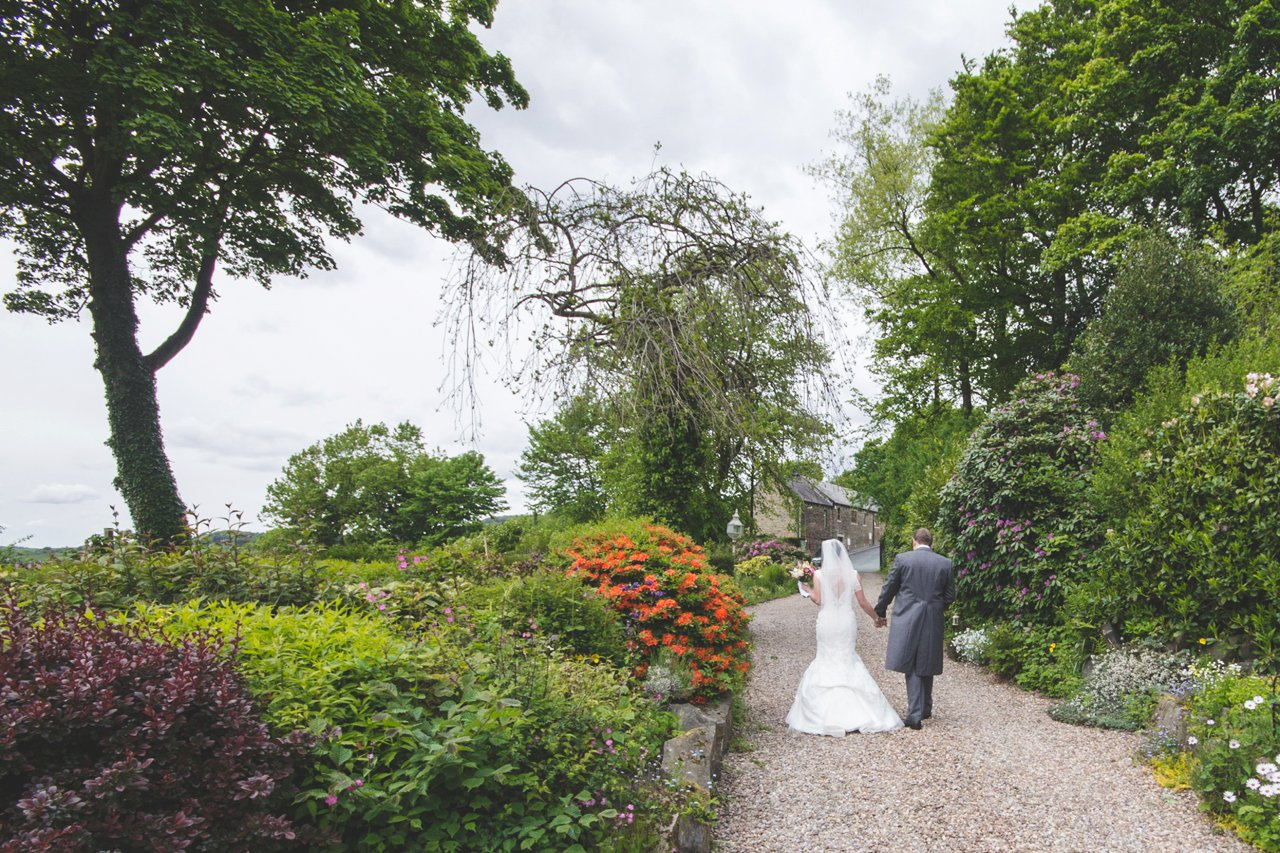 bride and groom walking up gravel path
