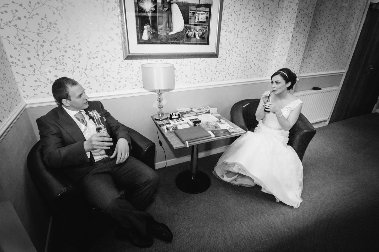 bride and groom relaxing on chairs at hotel
