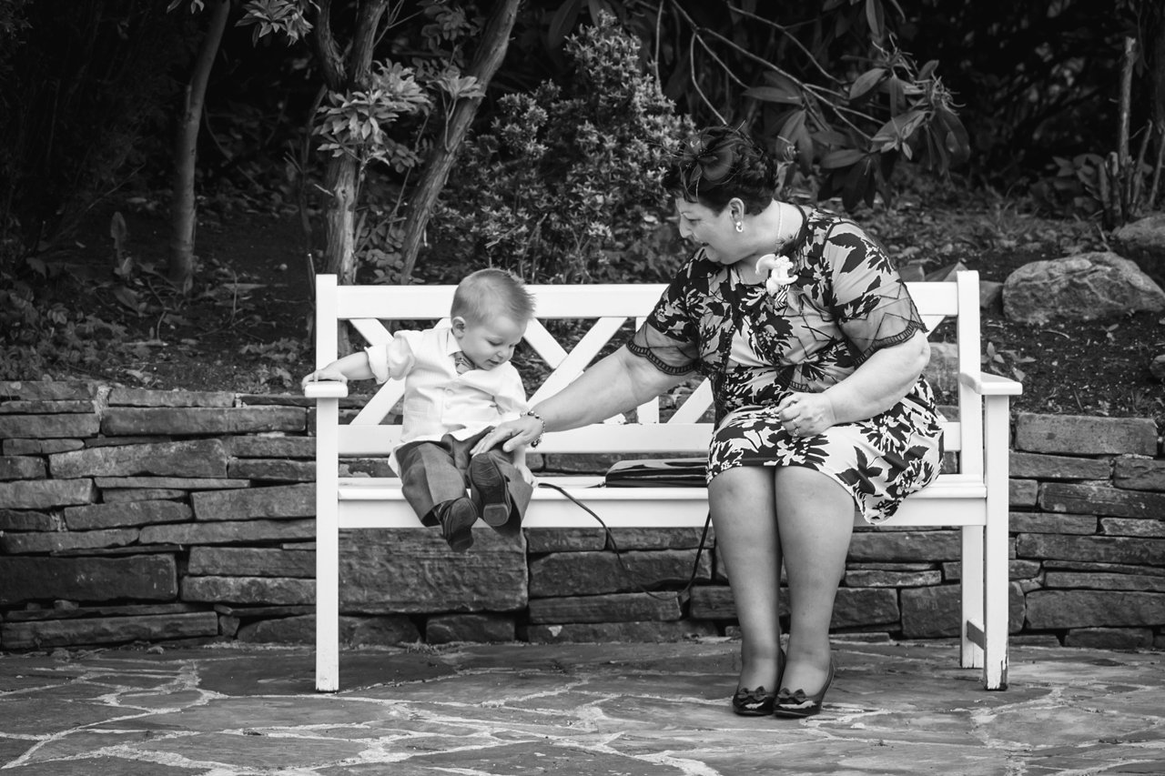 grandmother and grandson on white bench at wedding
