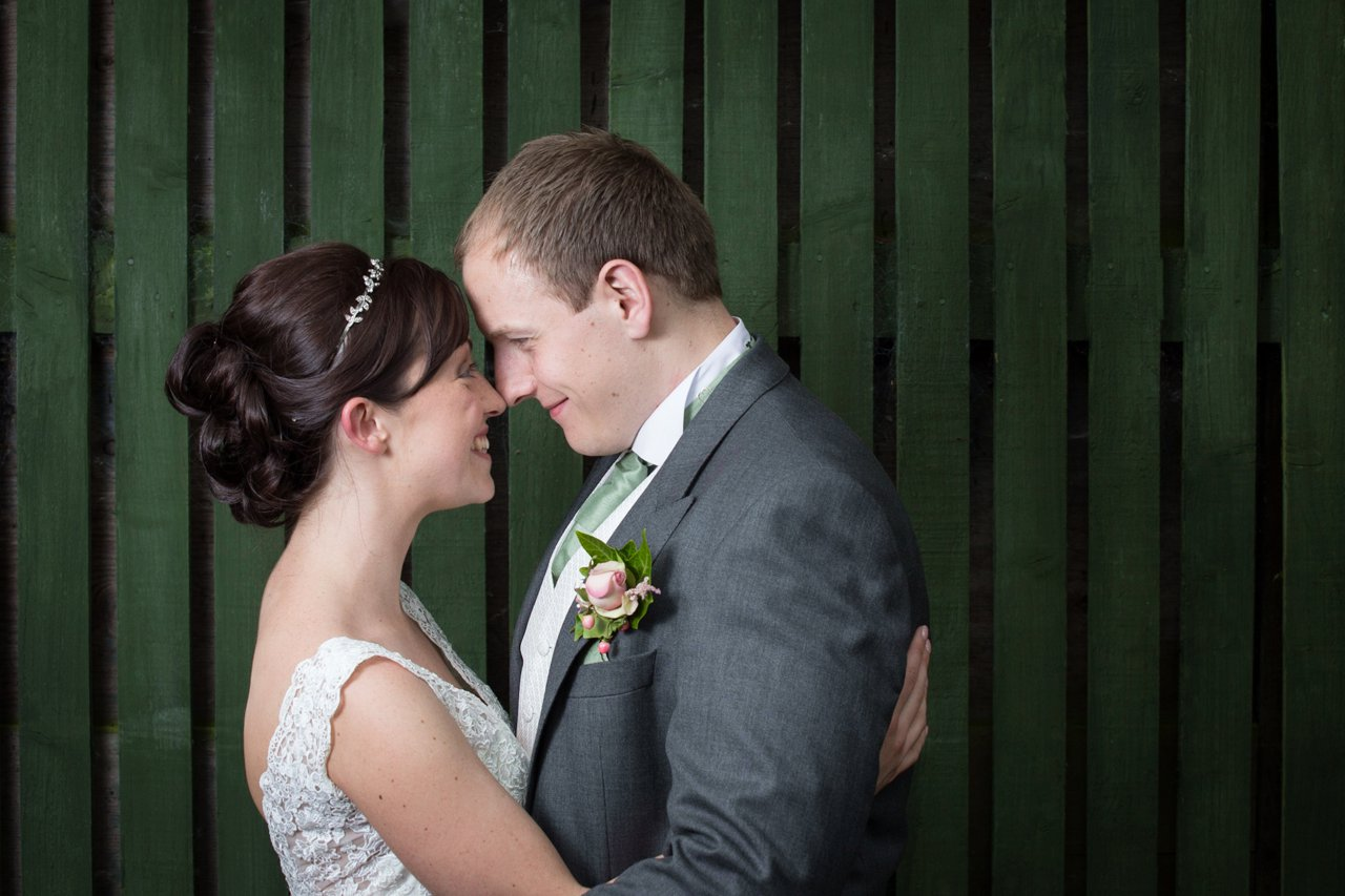 formal bride and groom against green wooden background