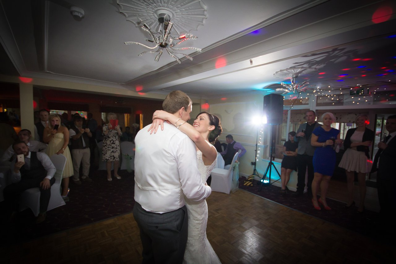 first dance smiling bride embracing on dancefloor with disco lights