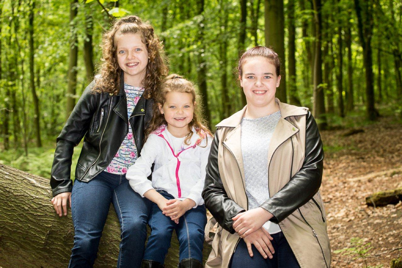 children sat on fallen tree in woodland