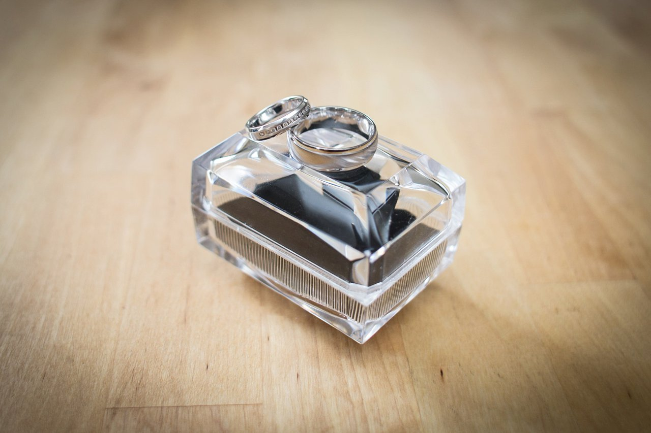 detail of wedding rings on top of glass box on wooden table