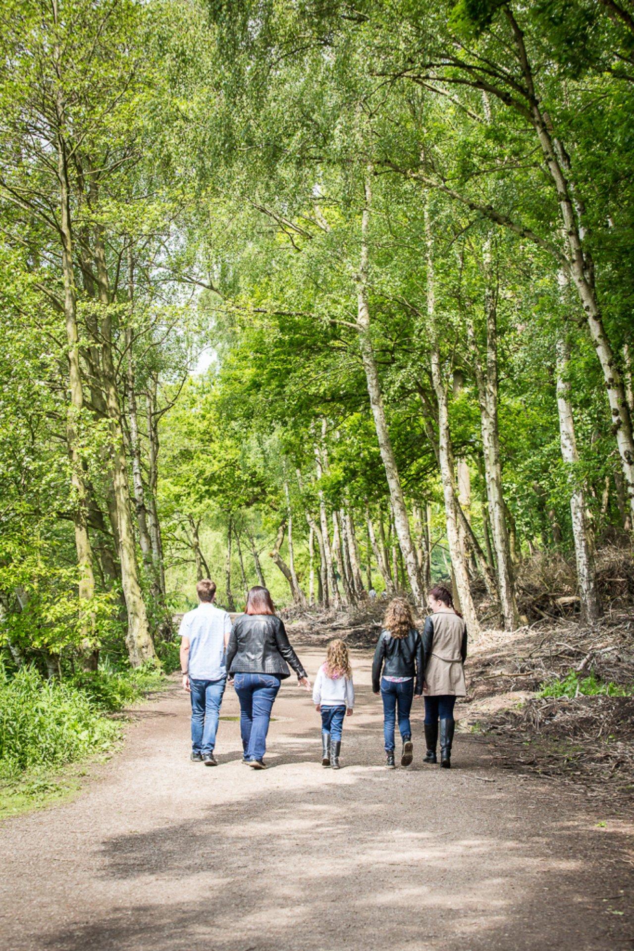 family walking away down woodland path