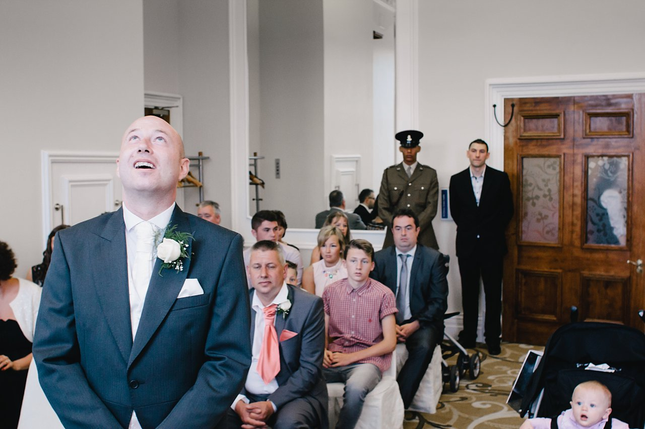nervous and thoughtful groom waiting for bride at registry office