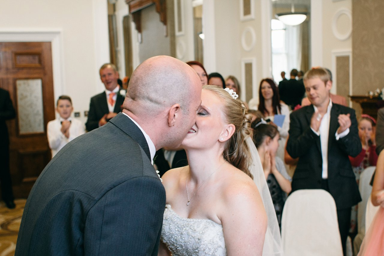 bride and groom kiss at Huddersfield Town Hall