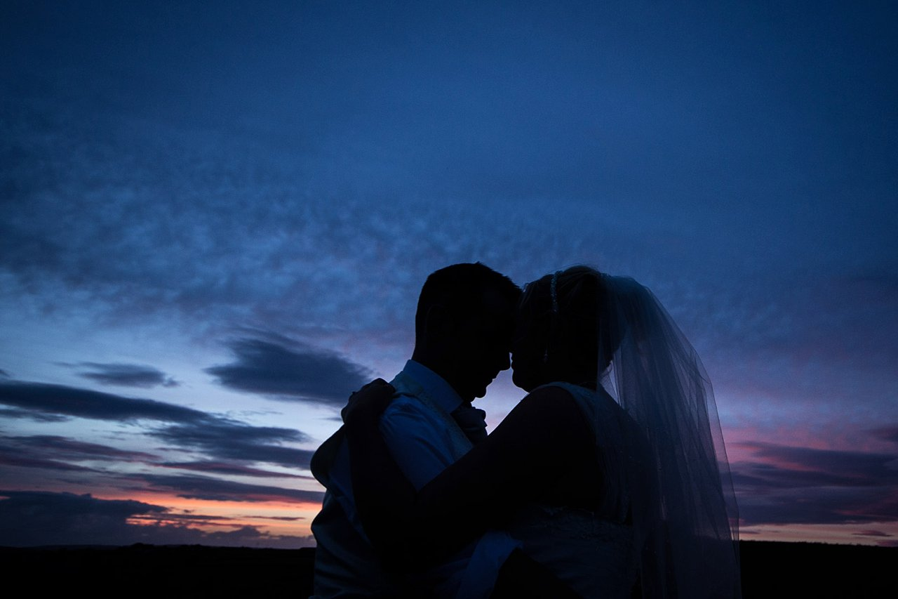 bride and groom silhouetted against sunset
