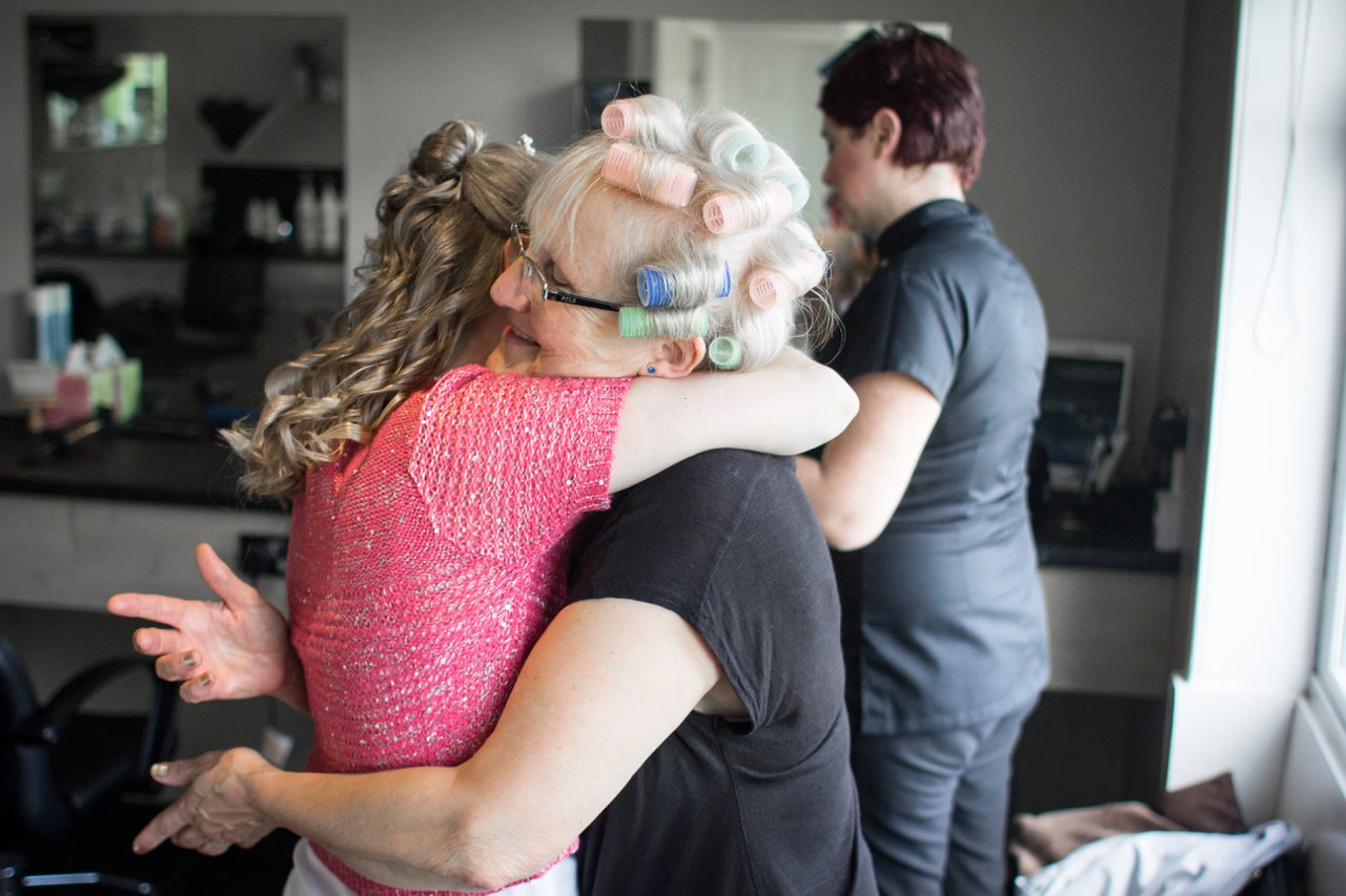 bride hugs mother in hairdressing salon
