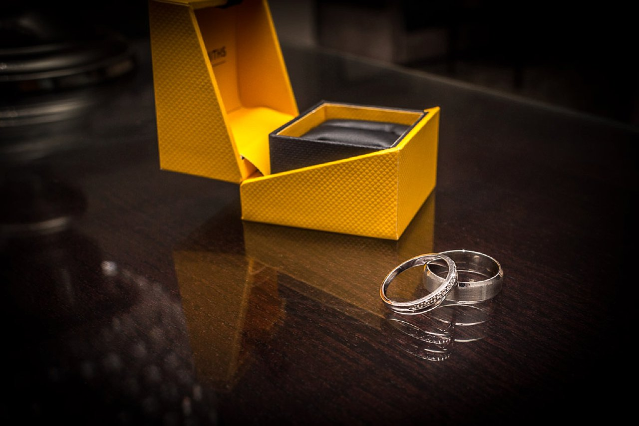 wedding rings with yellow box on glass reflective table