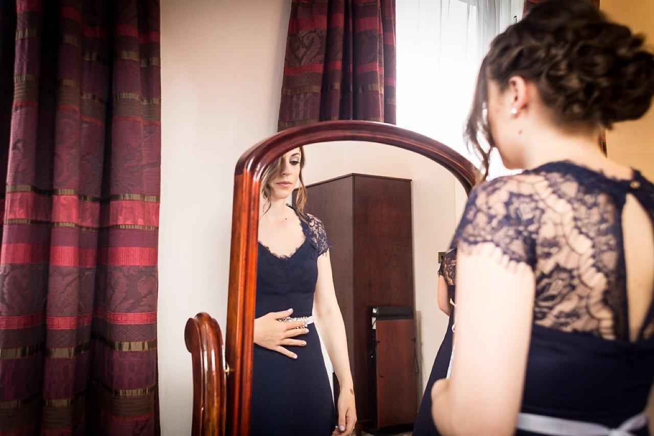 Bridesmaid standing at mirror