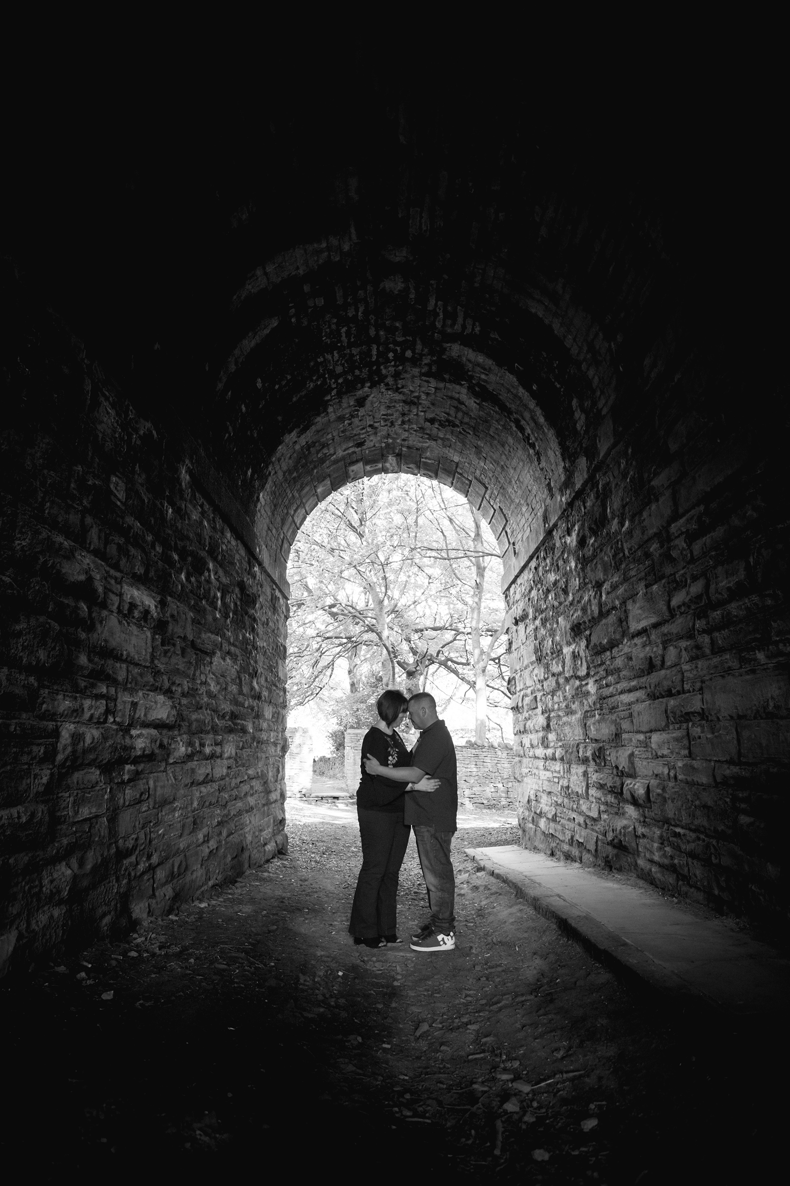 Couple kissing in tunnel, black and white