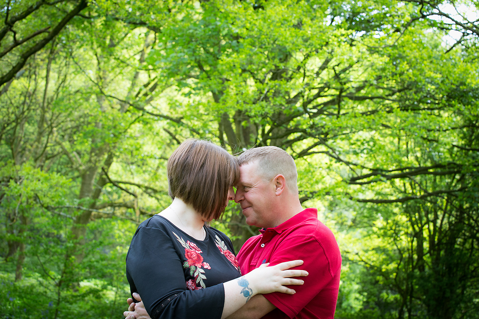 Couple embracing in front of green trees, Shibden Hall Halifax